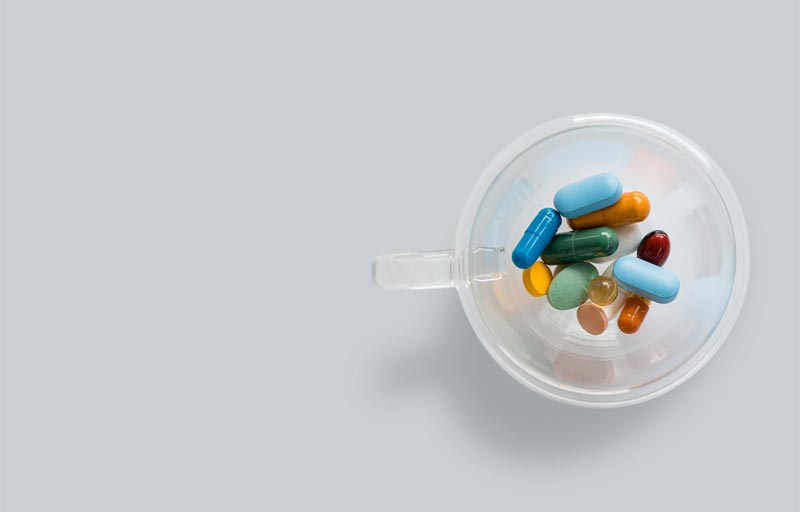 Different coloured pills in a mug, MyClinic provides E-prescription